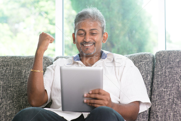 Indian man cheering while using tablet pc Stock photo © szefei