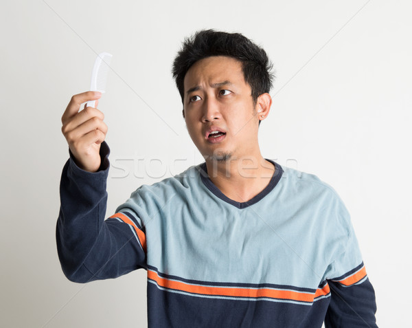 Man checking on a comb with shock face Stock photo © szefei