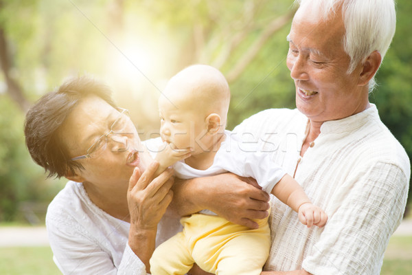Grandparents and grandchild outdoors. Stock photo © szefei