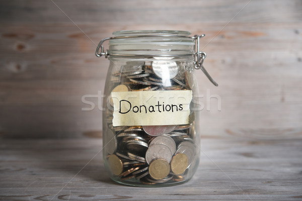 Stock photo: Money jar with donations label.