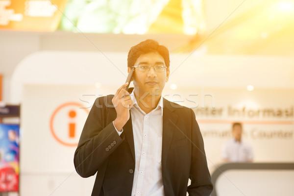 Indian businessman walking by information counter Stock photo © szefei