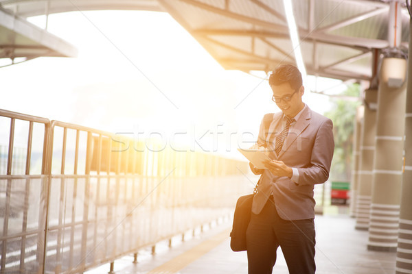 Businesspeople using tablet pc while waiting train. Stock photo © szefei