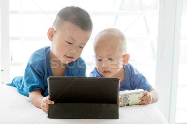 Children addicted to tablet. Stock photo © szefei