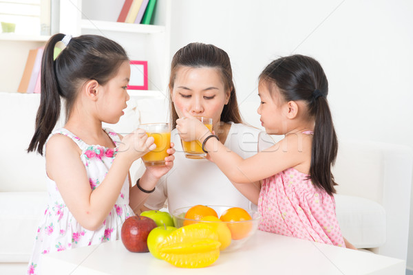 Asian parent and children drinking orange juice Stock photo © szefei
