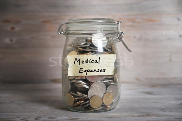 Money jar with medical expenses label. Stock photo © szefei