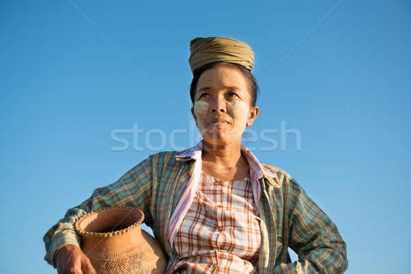 Mature Asian traditional female farmer carrying clay pot Stock photo © szefei