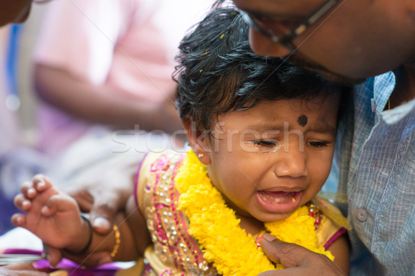 Baby girl crying in ear piercing ceremony Stock photo © szefei