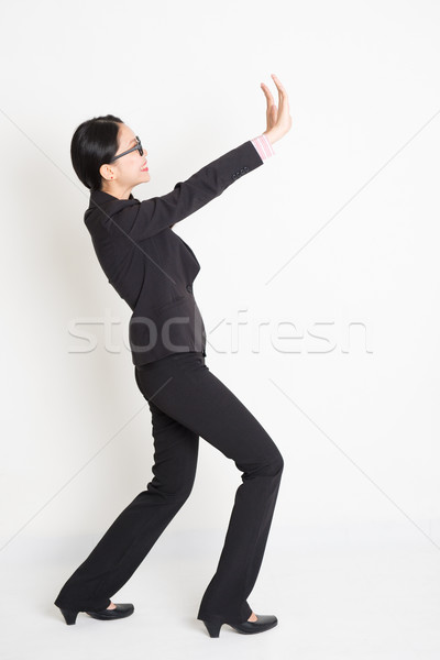 Asian businesswoman lifting something heavy Stock photo © szefei