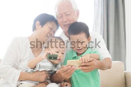Grootouders kleinkinderen smart telefoons portret gelukkig Stockfoto © szefei