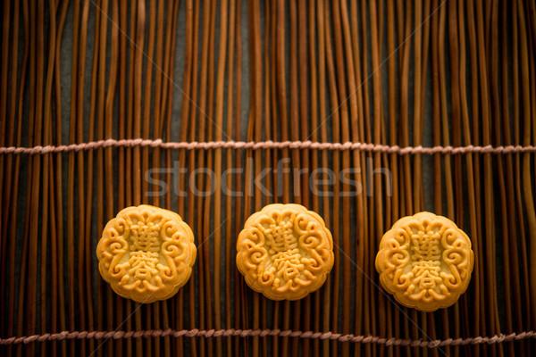 Mooncakes on bamboo mat with copy space dark light Stock photo © szefei