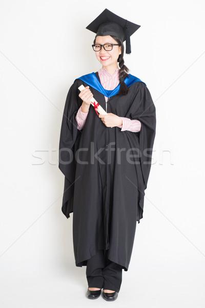 Egészalakos egyetemi hallgató érettségi talár sapka tart Stock fotó © szefei