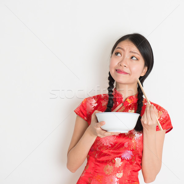 Asian chinese girl eating and thinking Stock photo © szefei