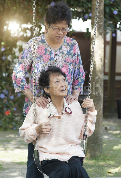 Asian elderly women playing swing at outdoor playground Stock photo © szefei