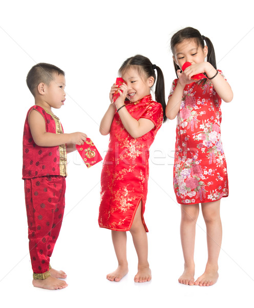 Asian children peeking into red packet  Stock photo © szefei