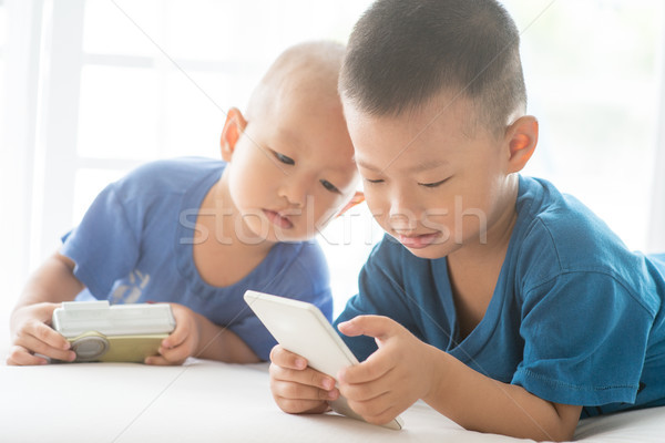 Children addicted to smart phone. Stock photo © szefei