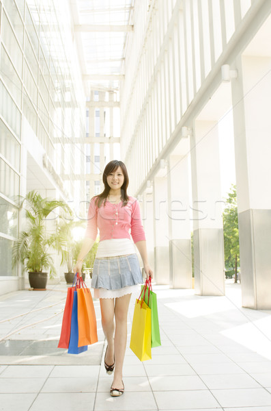 Stock photo: Asian woman walking out from shopping mall