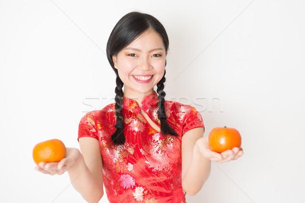 Oriental woman in red qipao holding mandarin orange Stock photo © szefei