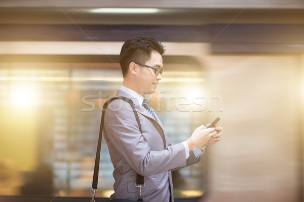 Businessman using smartphone at subway station. Stock photo © szefei