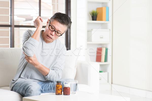 érett ázsiai férfi könyök fájdalom portré Stock fotó © szefei