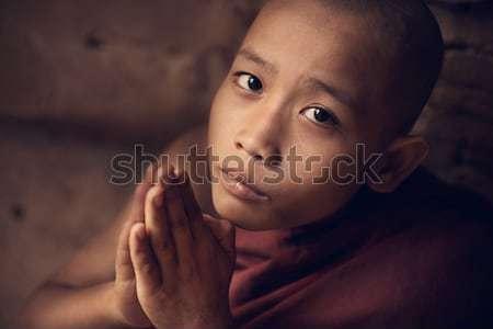 Buddhist novice monk praying in monastery Stock photo © szefei