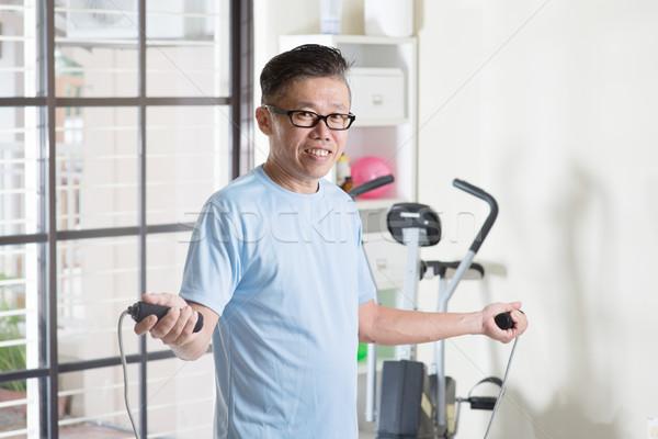 Mature Asian man doing rope skipping exercise Stock photo © szefei