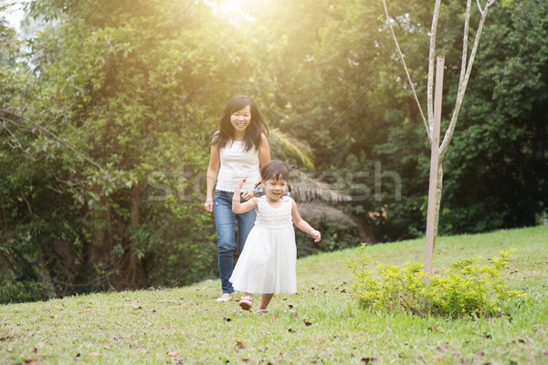 Mother and little girl chasing outdoors Stock photo © szefei