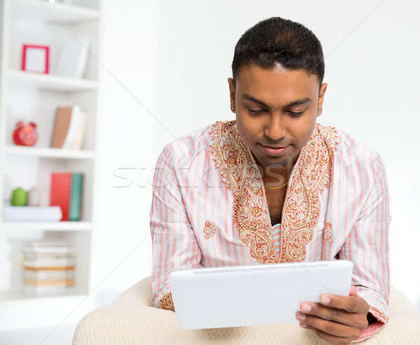 Indian man using digital tablet pc at home. Stock photo © szefei