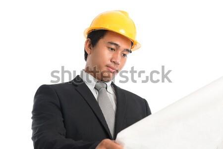 Asian male wearing yellow hardhat looking blue print paper. Stock photo © szefei