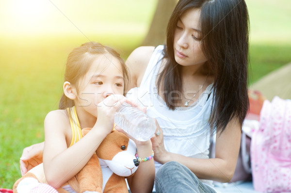 Madre confortevole bambino acqua potabile asian piangere Foto d'archivio © szefei