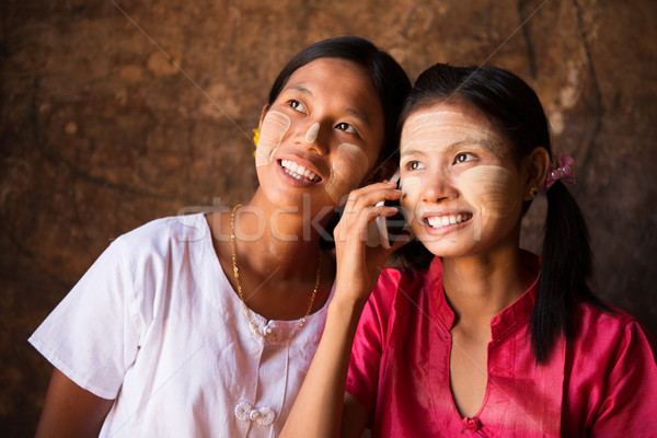Two Myanmar girls using smart phone. Stock photo © szefei