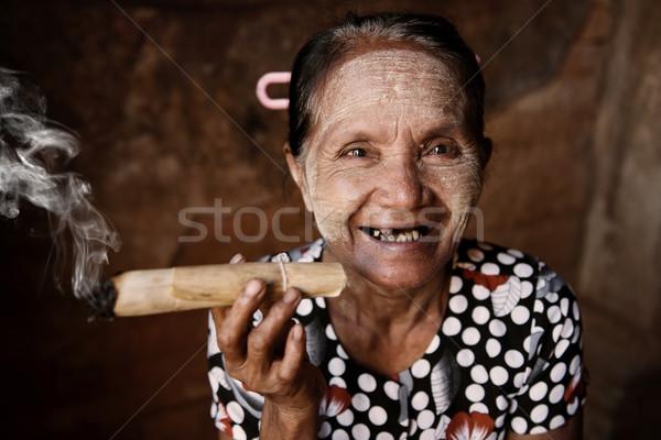 Happy old wrinkled Asian woman smoking  Stock photo © szefei