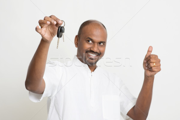 Indian man holding car key and thumb up Stock photo © szefei