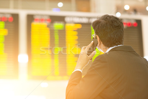 Businessman looking at airport flight timetable Stock photo © szefei