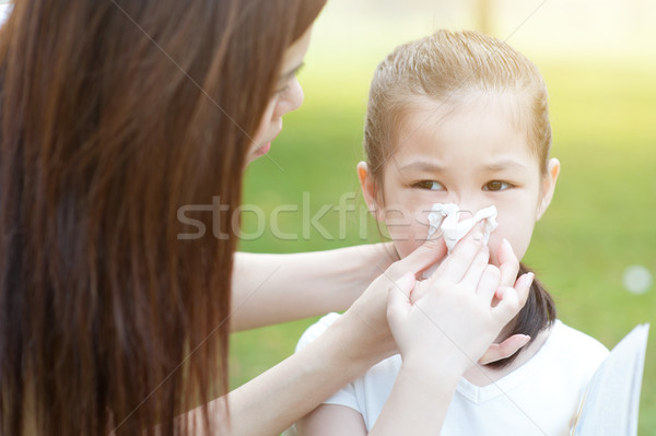 Allergy. Little girl blowing nose. Stock photo © szefei