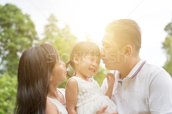 Szczęśliwą rodzinę klejenie odkryty rodziców całując dziecko Zdjęcia stock © szefei
