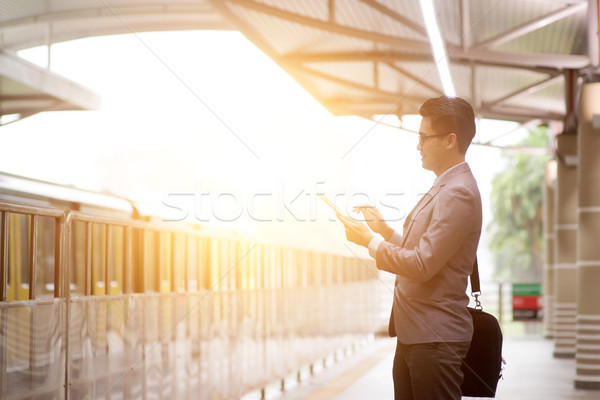 Business people using tablet pc while waiting train. Stock photo © szefei