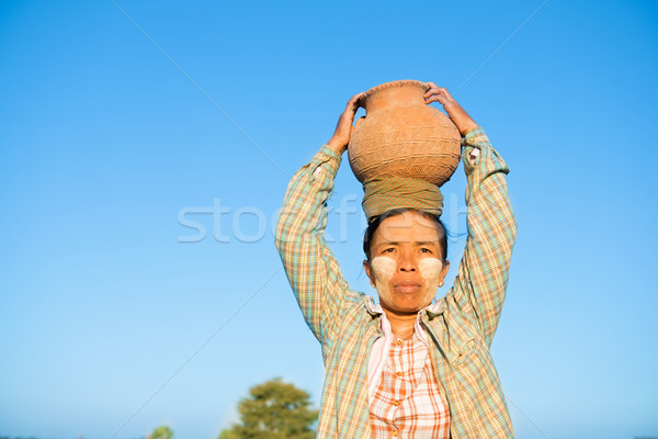 Mature Asian traditional female farmer carrying clay pot on head Stock photo © szefei