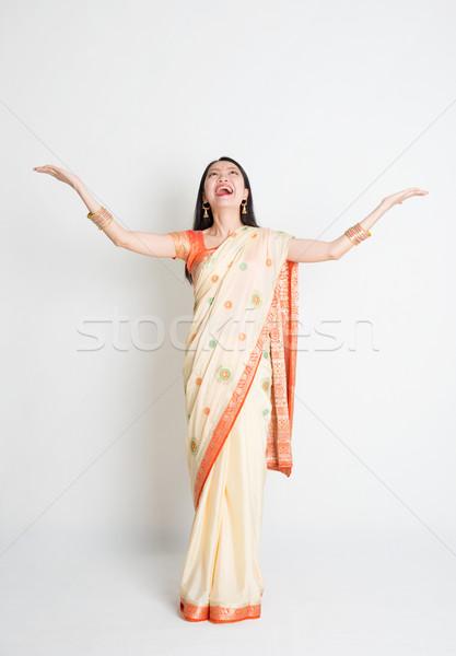 Woman in Indian sari dress hand raised looking up Stock photo © szefei