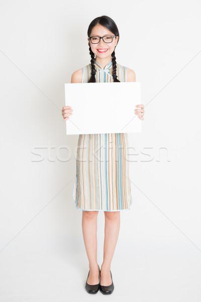 Oriental girl holding white paper card Stock photo © szefei