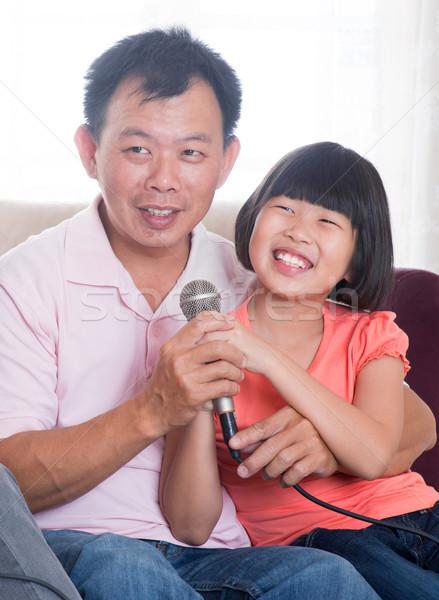 Happy Asian family singing karaoke  Stock photo © szefei