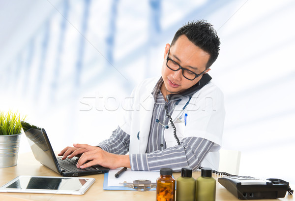 Busy Southeast Asian medical doctor  Stock photo © szefei