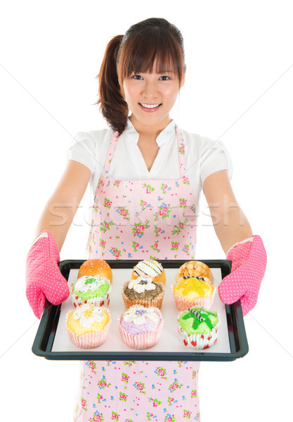 Young Asian female baking bread and cupcakes Stock photo © szefei