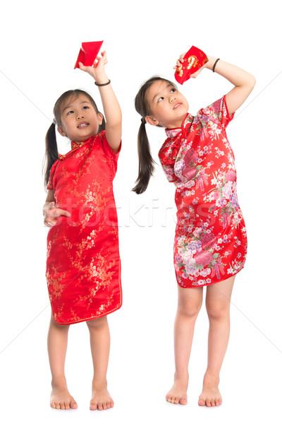 Asian girls peeking into red packet Stock photo © szefei