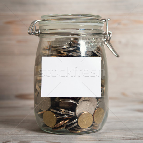 Coins in glass money jar with white blank label Stock photo © szefei