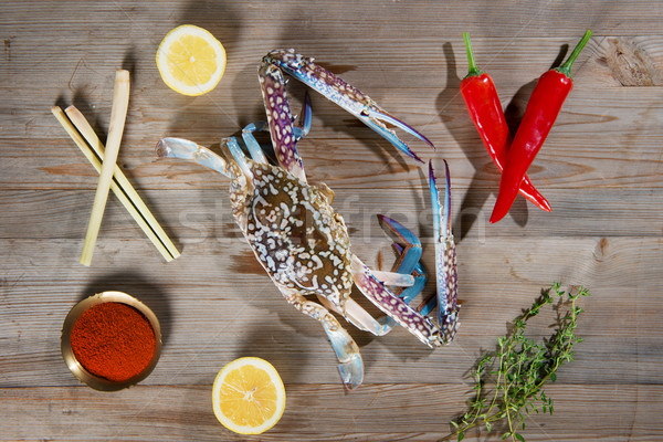 Raw blue crab and ingredients on wood plank Stock photo © szefei