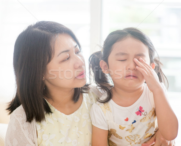 Mother comforts crying daughter. Stock photo © szefei