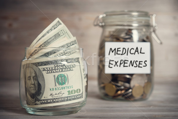 Stock photo: Dollars and coins in jar with medical expenses label
