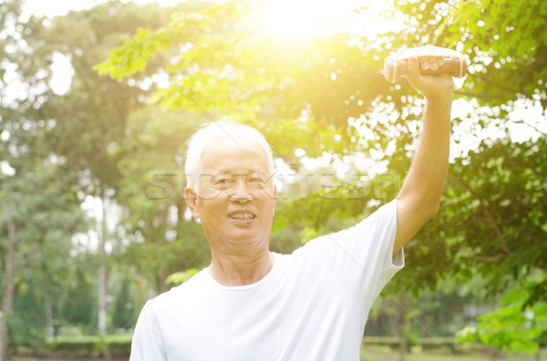 Asian old man playing dumbbell in the park  Stock photo © szefei