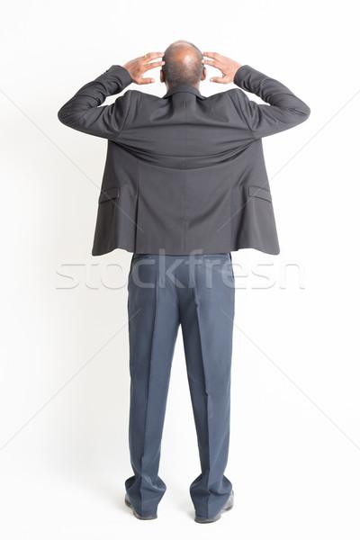 Rear view  full length mature Indian businessman scratching head Stock photo © szefei