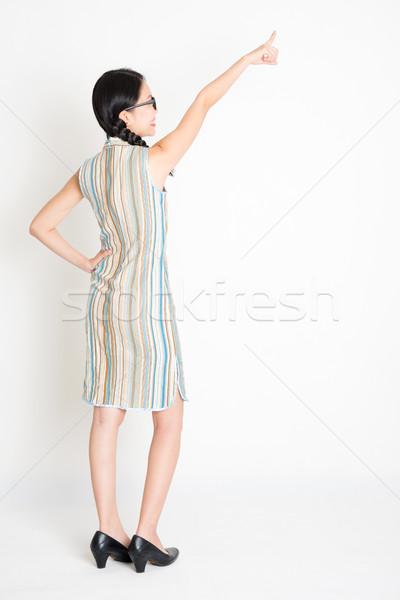 Asian girl pointing away Stock photo © szefei